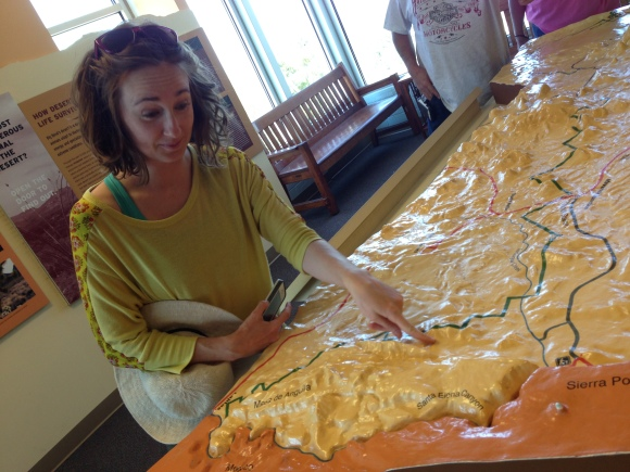 """Jenna utilizes to topographical map at the headquarters to make tomorrow's hike look like """"no biggie."""""""